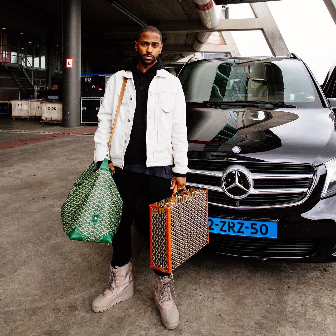 Big Sean Wearing A John Elliott Jacket, Carhartt Hoodie, Yeezy Boots And Goyard Luggage